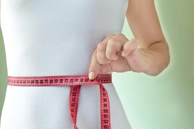 La mujer mide su cintura.