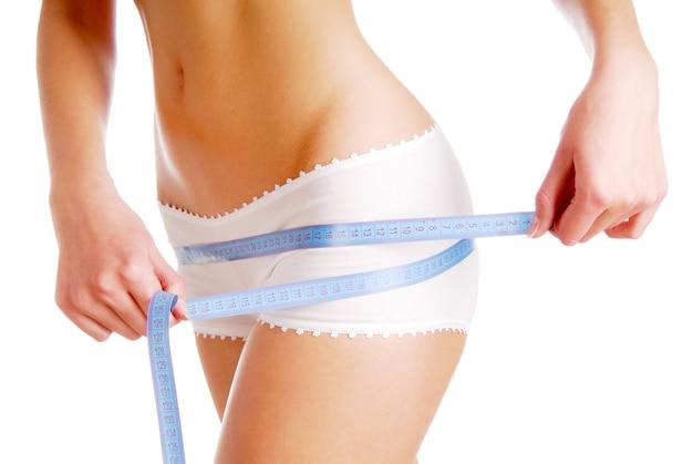Mujer midiendo la forma perfecta de hermosas caderas