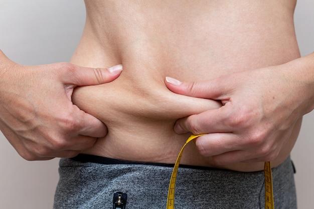 Mujer midiendo la grasa. chequeo corporal. concepto de dieta de fitness.