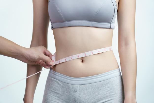 Mujer midiendo su cintura con cinta métrica.