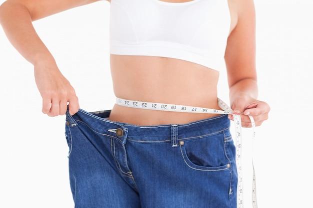 Mujer midiendo su cintura mientras usa jeans demasiado grandes