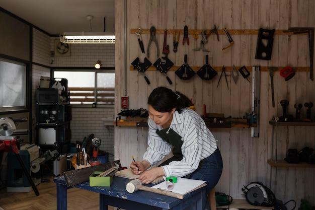 Mujer midiendo tiro medio de madera