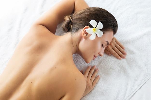 La mujer miente y se relaja después de una sesión de masaje