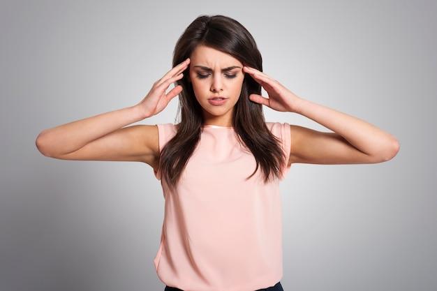 Mujer con migraña masajeando sus sienes