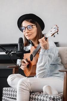 Mujer milenaria caucásica en un sombrero con un micrófono, tocando la guitarra o el ukelele