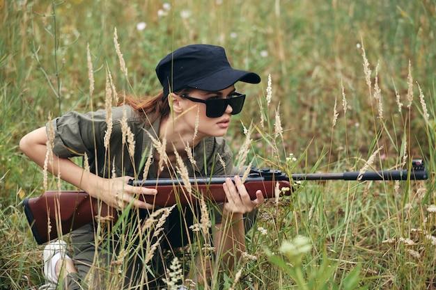 Mujer militar cazando con escopeta y gafas de sol