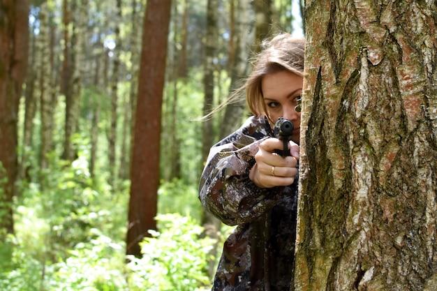 Mujer militar dispara con una pistola en el bosque. chica cazadora escondida detrás de un árbol con armas.