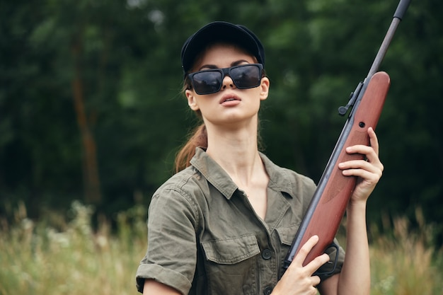 Mujer militar escopeta caza gafas de sol hojas verdes