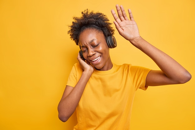 Mujer millennial de piel oscura despreocupada tiene movimientos divertidos con el ritmo de la música que mantiene el brazo levantado