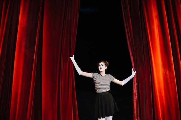 Mujer mime artista sosteniendo la cortina roja