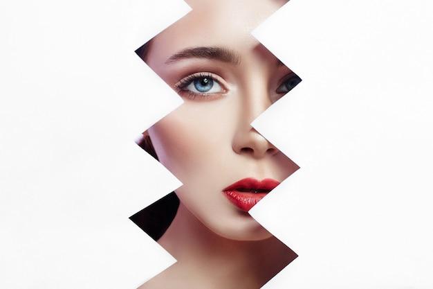 Mujer mira en agujero rasgado de papel, maquillaje brillante