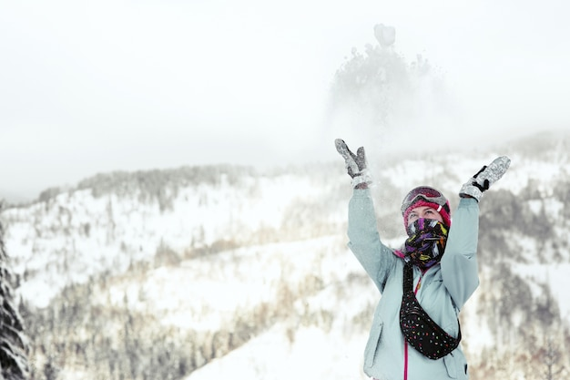 La mujer mira cómo cae la nieve en su cara mientras posa en la montaña de invierno