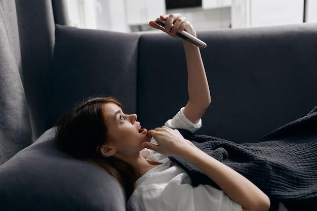 Una mujer mira la pantalla del teléfono y se acuesta en el sofá debajo de una manta gris