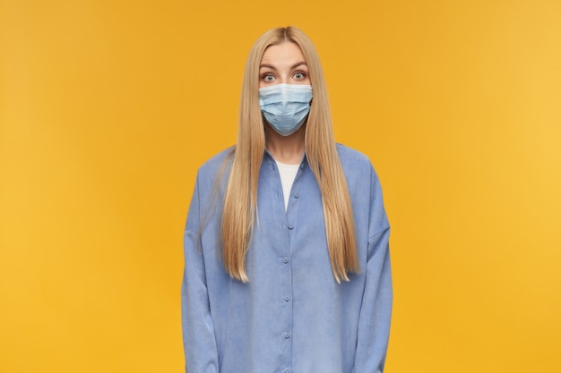 Mujer de mirada asombrada, hermosa chica con cabello largo y rubio. vistiendo camisa azul y mascarilla médica. concepto de personas y emociones. mirando a la cámara, aislada sobre fondo naranja
