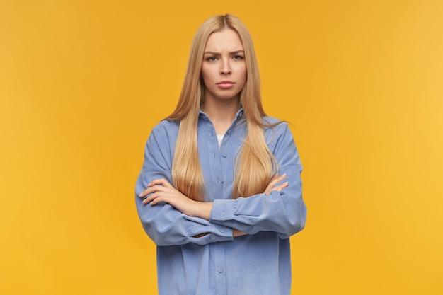 Mujer de mirada seria, hermosa chica con cabello largo y rubio. vistiendo camisa azul. concepto de personas y emociones. mantiene los brazos cruzados sobre el pecho. mirando a la cámara, aislada sobre fondo naranja