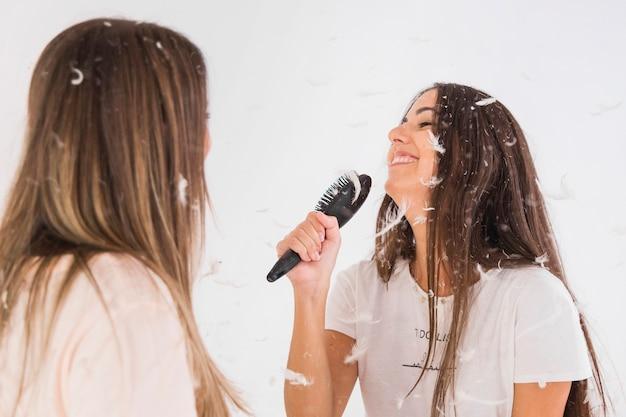 Mujer mirando a su amigo cantar canción con peine como un micrófono