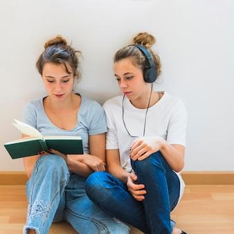 Mujer mirando a su hermana leyendo el libro sentado en el piso de madera