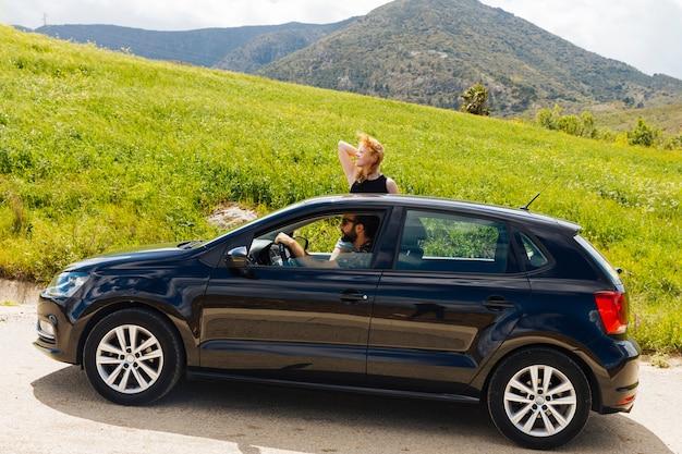 Mujer mirando hacia adelante saliendo de la ventana del coche