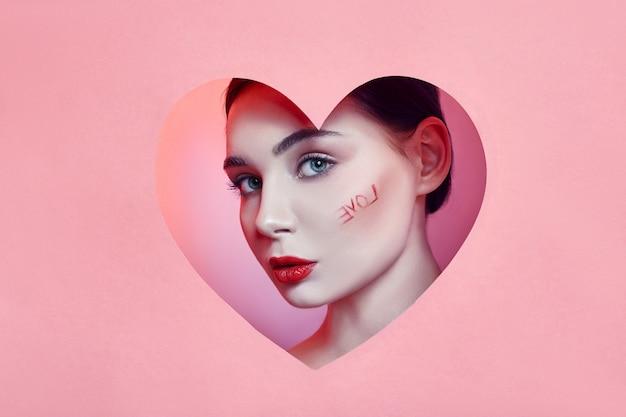Mujer mirando en el agujero del corazón, maquillaje hermoso brillante, ojos grandes y labios