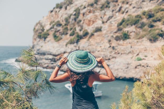 Mujer mirando al mar y sosteniendo su sombrero en la orilla del mar en camisa negra durante el día