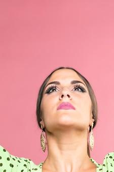 Mujer mirando hacia arriba con fondo rosa