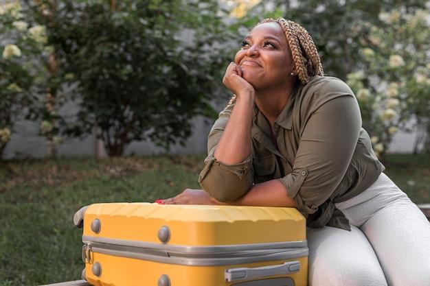 Mujer mirando hacia arriba junto a su equipaje amarillo