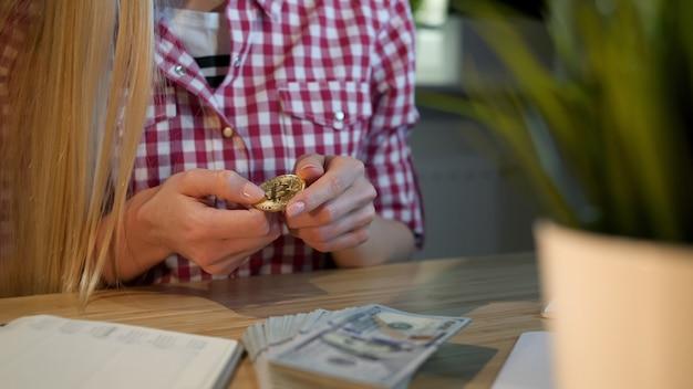 Mujer mirando atentamente bitcoin en manos