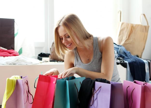 Mujer mirando en bolsas de compras