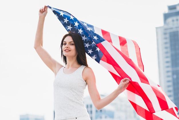 Mujer mirando a cámara y agitando bandera estadounidense