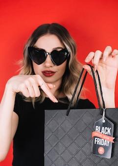Mujer mirando a la cámara y apuntando a la bolsa de viernes negro