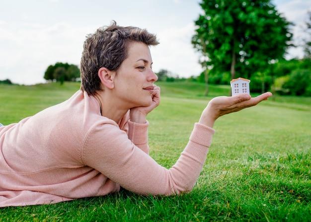 Mujer mirando la casa de juguete sobre hierba verde en el parque