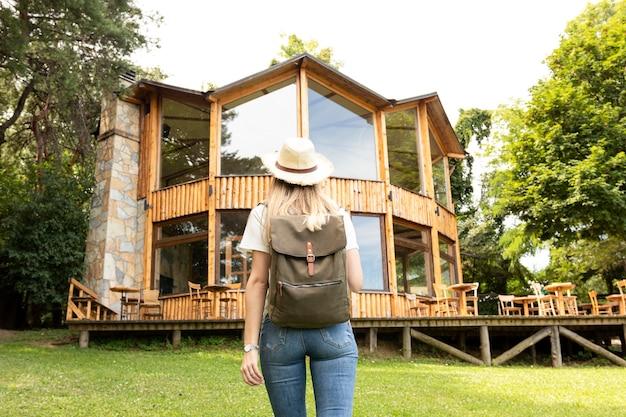 Mujer mirando la casa moderna desde atrás