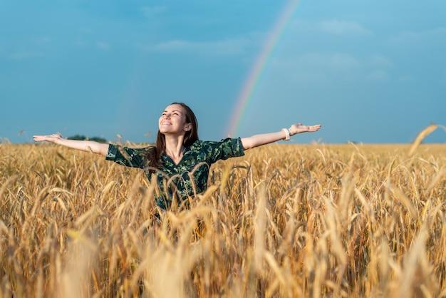 Mujer mirando hacia el cielo las manos a un lado en un campo con cereales en un arco iris