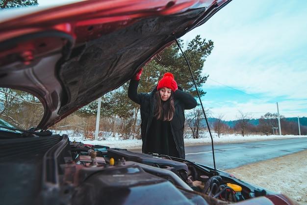 Mujer mirando el concepto de asistencia en carretera del motor del coche temporada de invierno