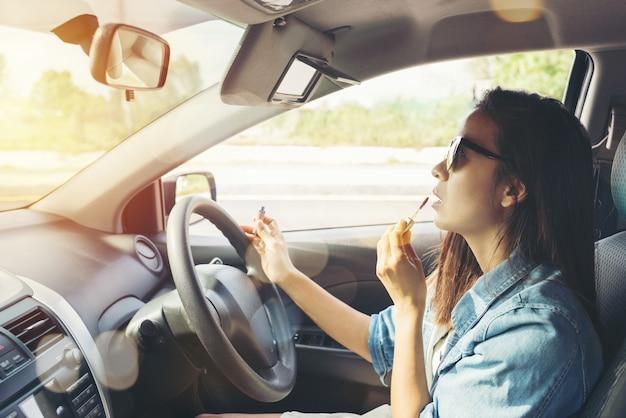 Mujer mirando en el espejo retrovisor y componiendo en coche