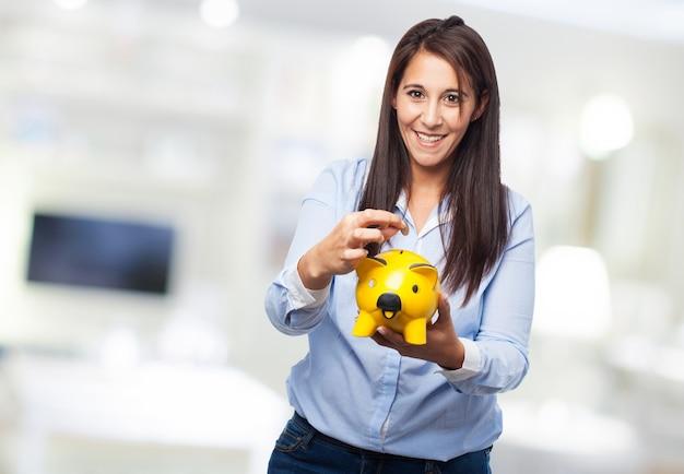 Mujer mirando la hucha de cerdito amarilla que tiene en sus manos