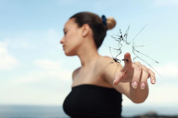 Mujer mirando a un lado mientras rompe un cristal con un dedo