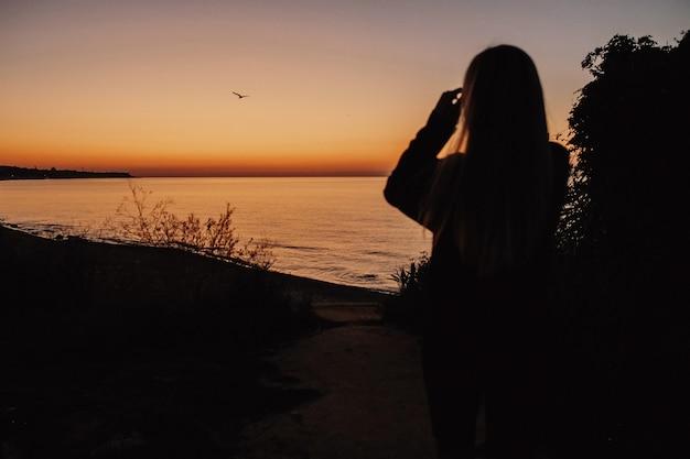 La mujer está mirando el lago de la tarde