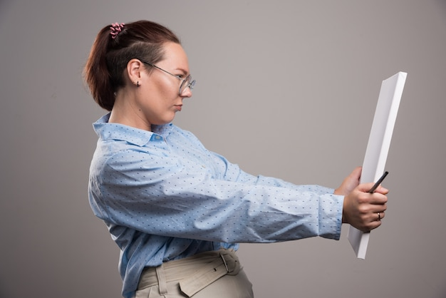 Mujer mirando lienzo vacío y pincel sobre fondo gris