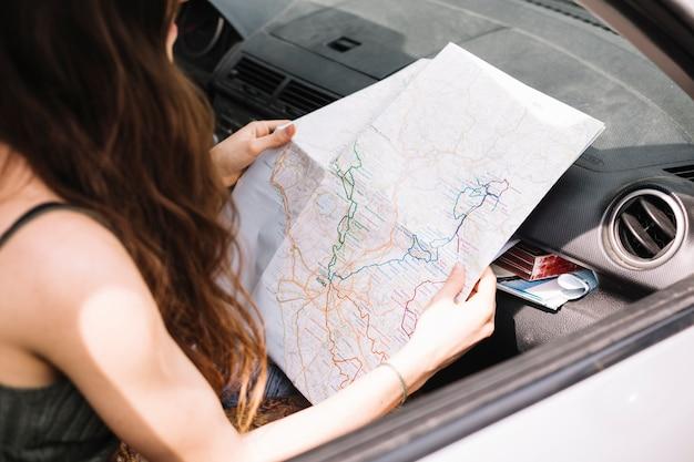 Mujer mirando a mapa en coche