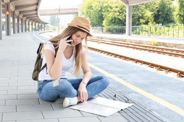Mujer mirando en un mapa en una estación de tren
