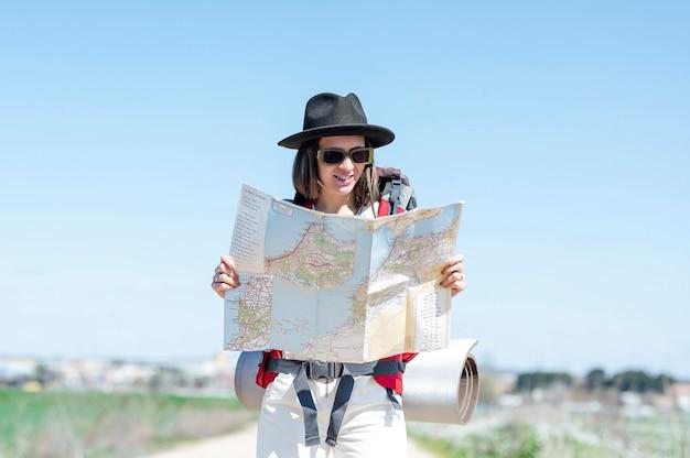 Mujer mirando un mapa viajar y explorar el concepto