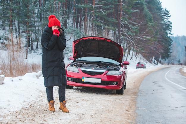 Mujer mirando el motor del coche roto en el espacio de copia lateral de la carretera de invierno