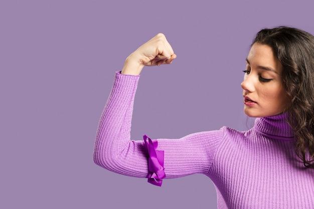 Mujer mirando orgullosamente los músculos de sus brazos