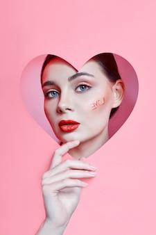 Mujer mirando en el orificio del corazón, maquillaje hermoso brillante, ojos grandes