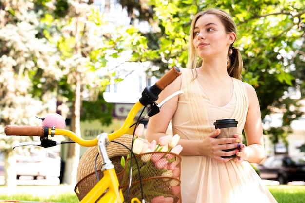 Mujer mirando a otro lado y apoyándose en una bicicleta