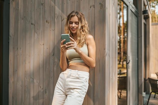 Mujer mirando la pantalla del teléfono inteligente con interés