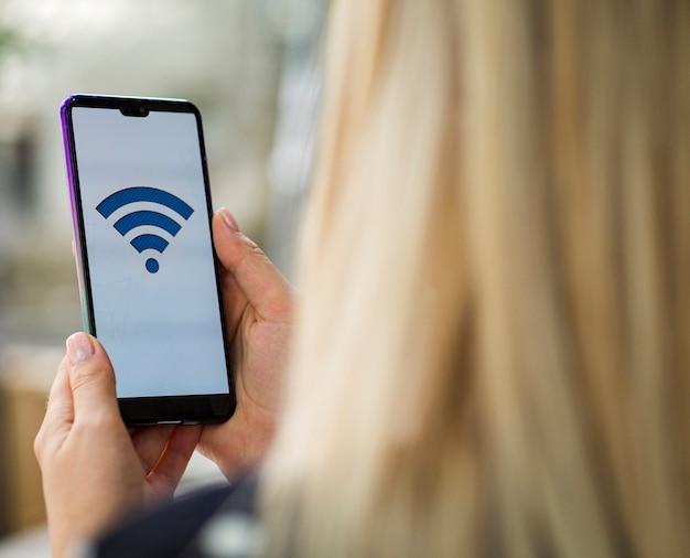 Mujer mirando la pantalla del teléfono con logo wifi