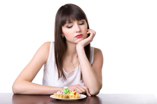 Mujer mirando con pena un plato con pasteles