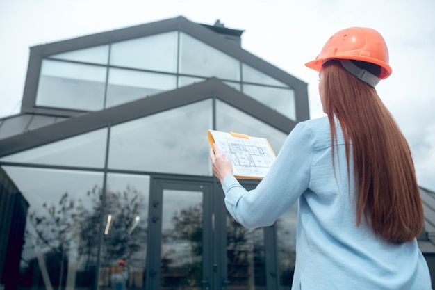 Mujer mirando plan de construcción y edificio